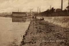"""Until 1930, when construction of the Western Docks led to huge land reclamation, there was a beach alongside the railway at Millbrook. The station footbridge is visible, and a """"down"""" train is due. (A Stewart collection)"""