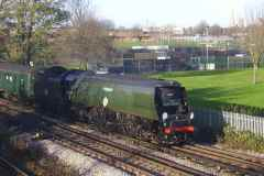 Holy Trinity church is in the distance, as preserved steam locomotive 34067 'Tangmere' passes on 28 November 2009, hauling a through train from Swanage to London.