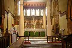 A closer view of the main altar, showing the carved alabaster reredos and murals either side. The Blessed Sacrament is reserved in the tabernacle.